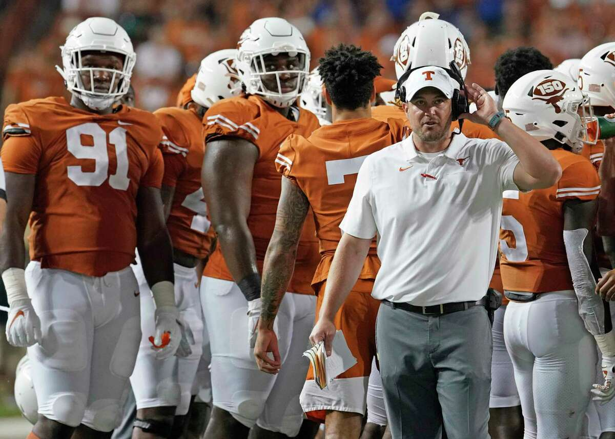 Texas coach Tom Herman, right, watches a replay during the second half of the team's NCAA college football game against Kansas in Austin, Texas, Saturday, Oct. 19, 2019. (AP Photo/Chuck Burton)