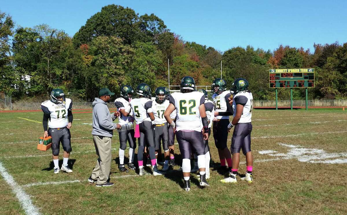 Coach Tim Nixon talks with the O'Brien Tech football offense before the start of the fourth quarter of the Condors' 44-0 win over MCW United at home in Ansonia on Saturday, Oct. 19, 2019.