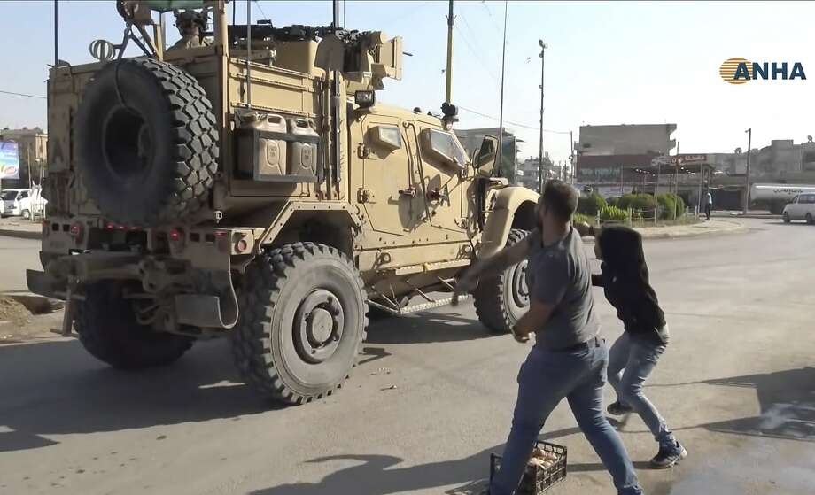 Syrians angry over U.S. withdrawal hurl potatoes at American military vehicles in the town of Qamishli. Photo: Associated Press