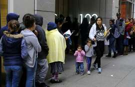 """File - In this Jan. 31, 2019, file photo, hundreds of people overflow onto the sidewalk in a line snaking around the block outside a U.S. immigration office with numerous courtrooms in San Francisco. Federal judges are being asked to block a new Trump administration policy scheduled to take effect next week that would deny legal permanent residency to many immigrants over the use of public benefits. Almost a dozen lawsuits have been filed from New York to California to prevent the """"public charge"""" rule from taking effect on Oct. 15. Judges have indicated a willingness to issue rulings before the scheduled start date. (AP Photo/Eric Risberg, File)"""
