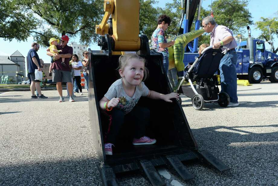 Charli Hill steps out from her seat inside a Caterpillar bucket during the Beaumont Children's Museum's annual Touch-a-Truck fundraiser Saturday.