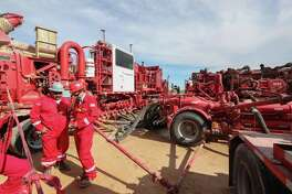 Halliburton employees work near rows of hydraulic fracturing pumping units at a three pad site Monday, June 26, 2017, in Midland. ( Steve Gonzales / Houston Chronicle )