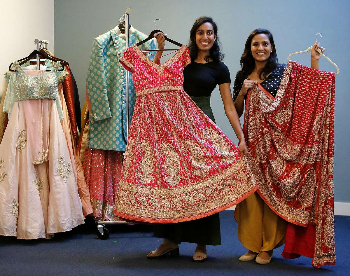 Sarina Siddhanti (l to r) and Arian Agrawal, co-founders Riya Collective, wear Indo western fusion casual clothes available for rent at Riya Collective as they hold a wedding gown with scarf available for rent at Riya Collective on Tuesday, October 15, 2019 in San Francisco, Calif. Agrawal's pants are by Salt and Spring.