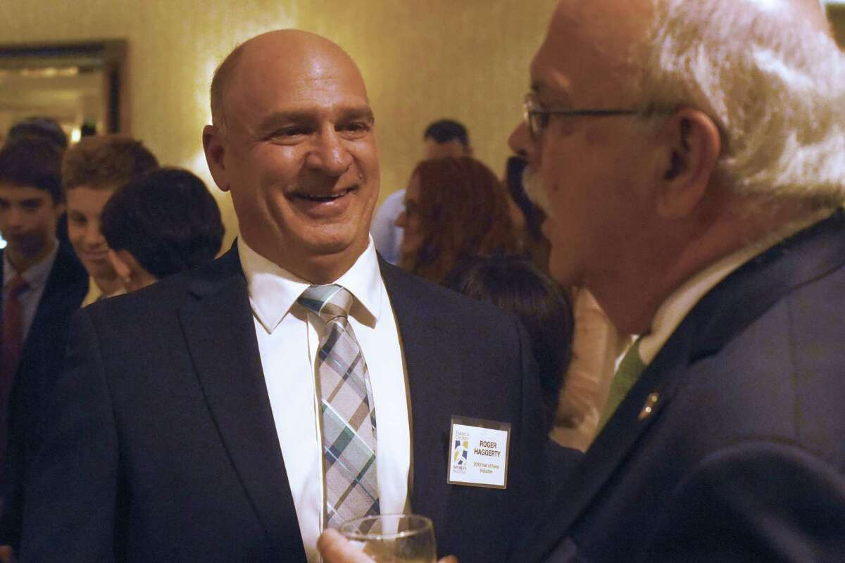 Stamford's Roger Haggerty shares a laugh with Roger Fox during the Fairfield County Sports Commission's annual Sports Night awards dinner at the Stamford Marriott on Monday. Haggerty was inducted into the FCSC Hall of Fame in the James O'Rourke Amateur Wing.