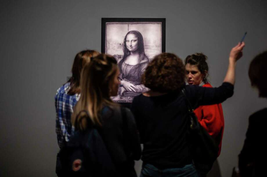 Journalists gather near a Mona Lisa image by Leonardo da Vinci during a visit at the Louvre museum Sunday, Oct. 20, 2019 in Paris. A unique group of artworks is displayed at the Louvre museum in addition to its collection of paintings and drawings by the Italian master. The exhibition opens to the public on Oct.24, 2019. (AP Photo/Rafael Yaghobzadeh) Photo: Rafael Yaghobzadeh / Copyright 2019 The Associated Press. All rights reserved