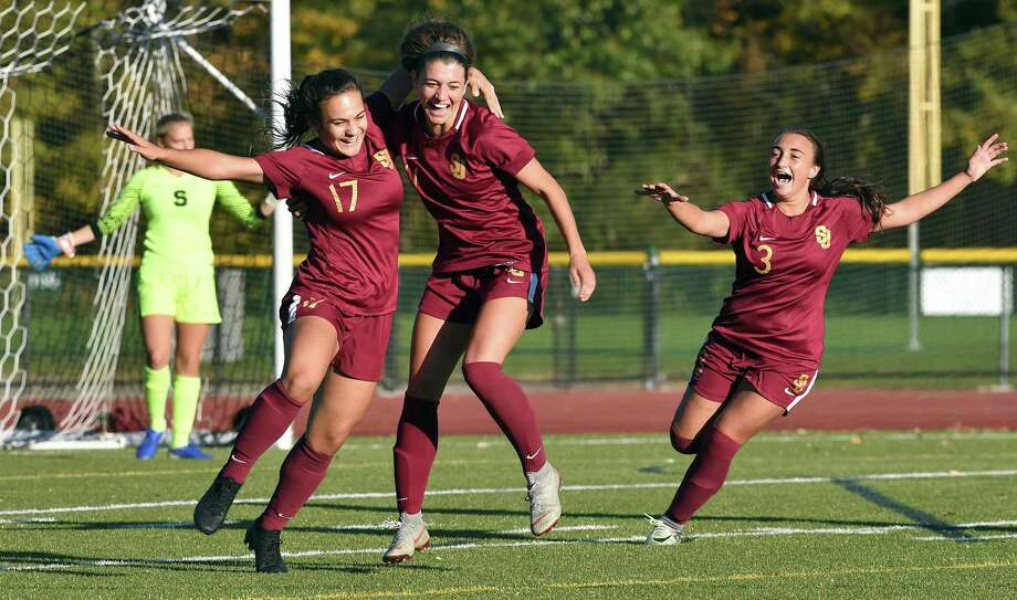 St. Joseph's Maddie Fried, center, celebrates with teammates Anastasia Kydes, left, and Andriana Cabral after scoring on a penalty kick in the second half on Monday. Photo: Arnold Gold / Hearst Connecticut Media / New Haven Register