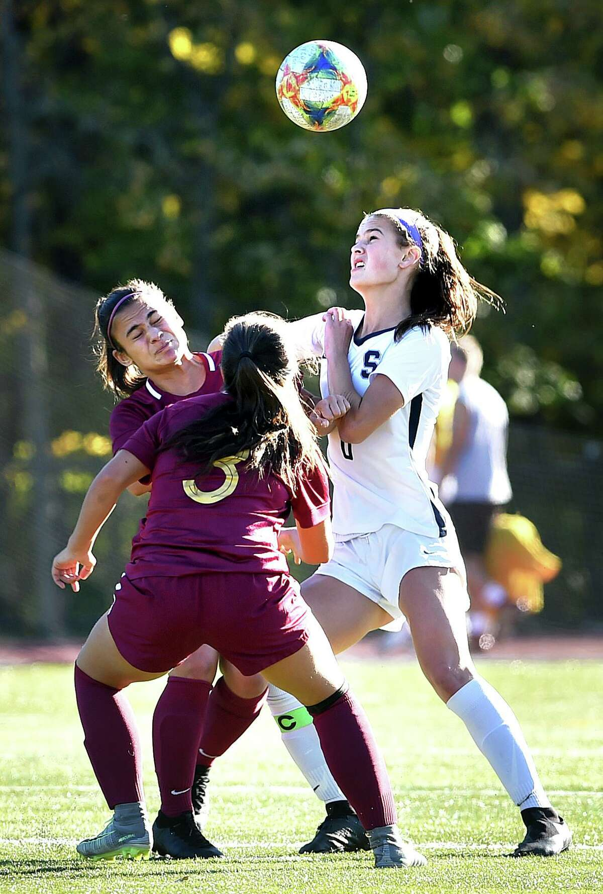 From left, St. Joseph's Anastasia Kydes and Andriana Cabral converge on a ball with Staples' Mia Gonzalez on Monday.