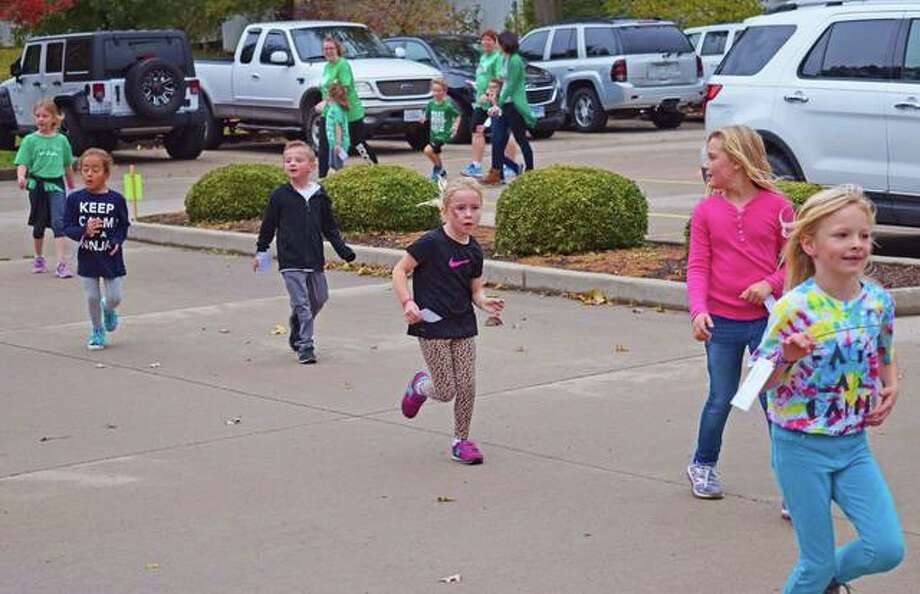 "Students race to the finish during Trinity Lutheran's Jog-a-thon on Monday in Edwardsville, in the spirit of ""Race for Education."""