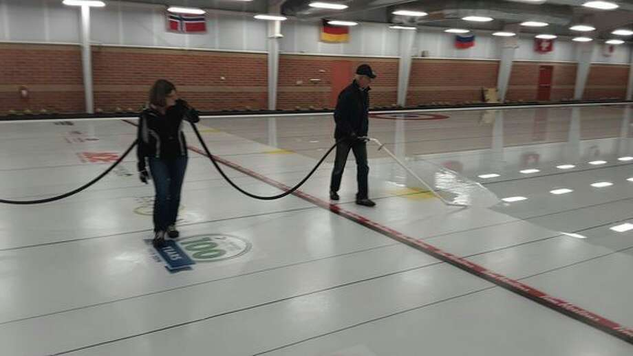 Ken Burdett, right, floods the ice at the Midland Curling Center while Brenda Mason helps hold up the hose. The flooding process must be repeated 11 times each October before the ice is thick enough for the curling season. (Dan Chalk/chalk@mdn.net)