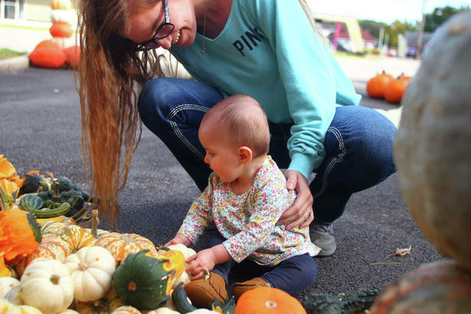 Madison Walters helps Madeilyn Dixon pick out a pumpkin at the JJ's Produce pumpkin stand on South Main Street. Photo: Rosalind Essig | Journal-Courier