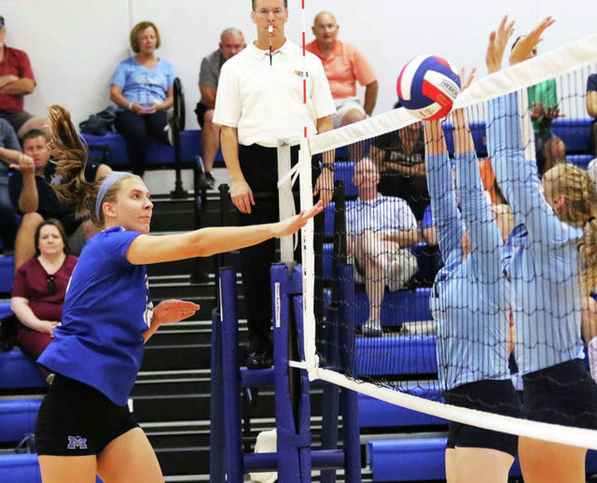 Marquette Catholic's Natalie Ellebracht (left) hits into the tape and the Jersey block during a Aug. 27 match at the Roxana Tourney. Ellebracht had three kills and three blocks in Marquette's loss Monday night at St. Louis Ursuline.