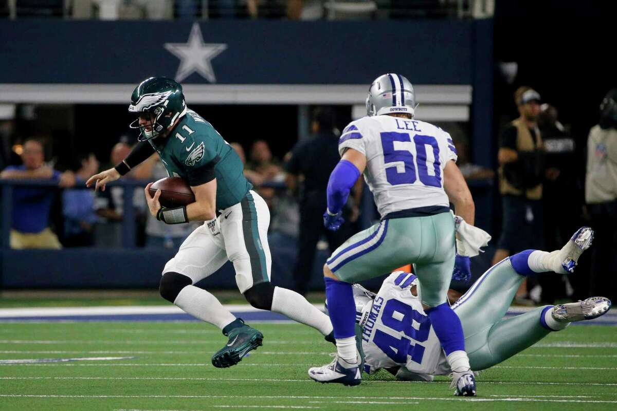 Philadelphia Eagles' Carson Wentz (11) evades pressure from Dallas Cowboys' Joe Thomas (48) and Sean Lee (50) during an NFL football game in Arlington, Texas, Sunday, Oct. 20, 2019. Shown on NBC, the game drew about 22 million viewers.