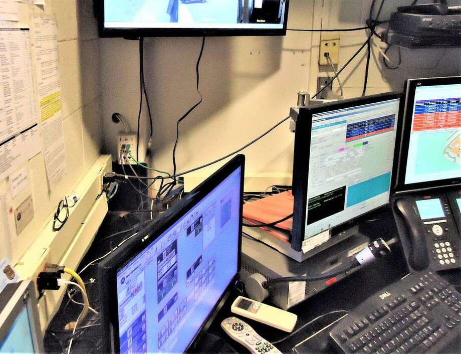 Dangling cords and wires can be seen in an overloaded area of the dispatch center of the Wilton Police Department. Photo: Wilton Police /Contributed Photo / Wilton Bulletin Contributed