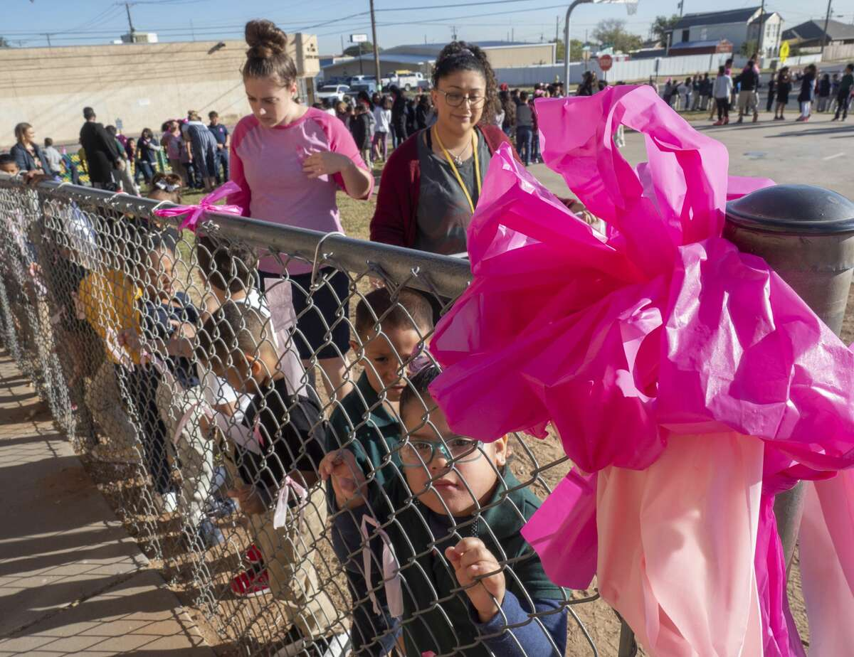 Students and teachers at South Elementary tie pink ribbons along the fence line 10/22/19 honoring staff members fighting breast cancer. Tim Fischer/Reporter-Telegram