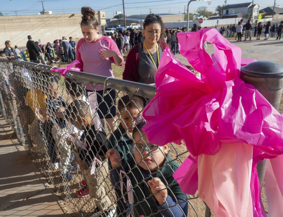 Students and teachers at South Elementary tie pink ribbons along the fence line 10/22/19 honoring staff members fighting breast cancer. Tim Fischer/Reporter-Telegram Photo: Tim Fischer/Midland Reporter-Telegram