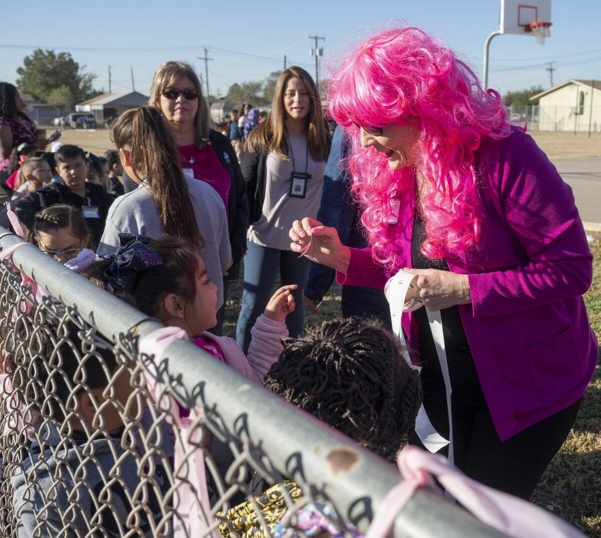 Debbie Bergen, cancer survivor, hands out pink ribbon stickers after South Elementary students and teachers tied pink ribbons along the fence line 10/22/19 honoring staff members fighting breast cancer. Tim Fischer/Reporter-Telegram