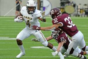 Kobe Banks (4) of Cy Ranch slips by Brady Matthews (23) of and Hunter Dade (32) of Cinco Ranch in the first quarter of a high school football game between the Cinco Ranch Cougars and the Cy Ranch Mustangs on Saturday, August 31, 2019 at Legacy Stadium, Katy, TX.