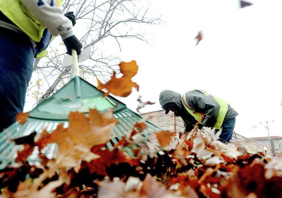 People rake leaves while bundling against dropping temperatures and gusty winds. Photo: Kim Brent / The Enterprise / BEN