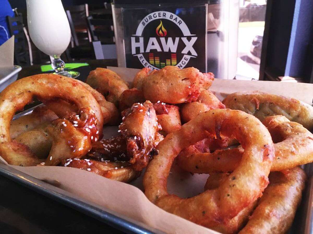 The Sample Me Some appetizer plate at Hawx Burger Bar includes fried pickle spears, wings, onion rings, fried mushroom and fried jalapeños.