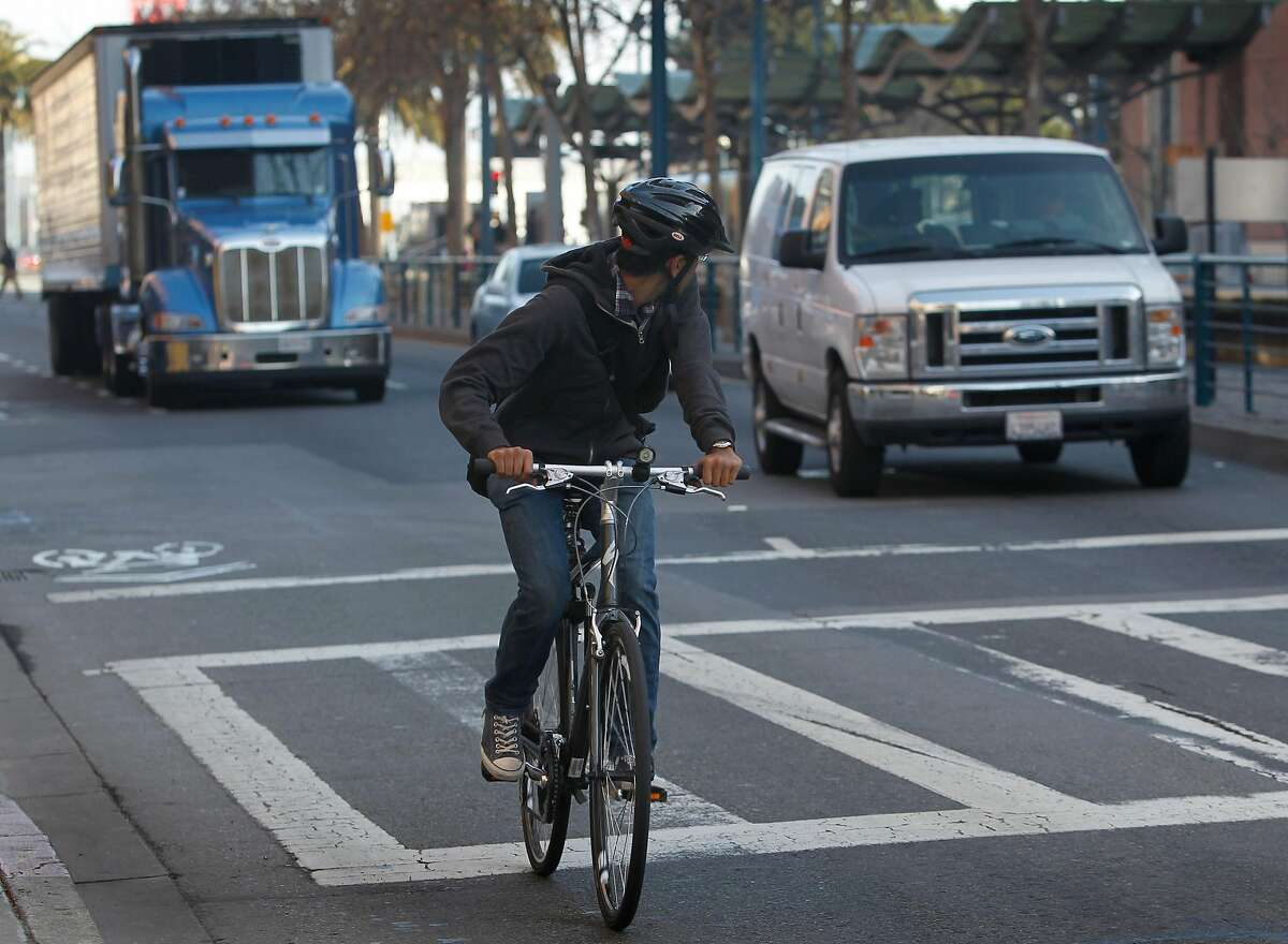 A bicyclist keeps an eye on traffic as he merges with vehicles at the end of a bike lane on King Street between 2nd and 3rd streets in San Francisco, Calif. on Tuesday, Feb. 12, 2013. A woman riding her bicycle was struck and killed after she collided with a cement truck last weekend.