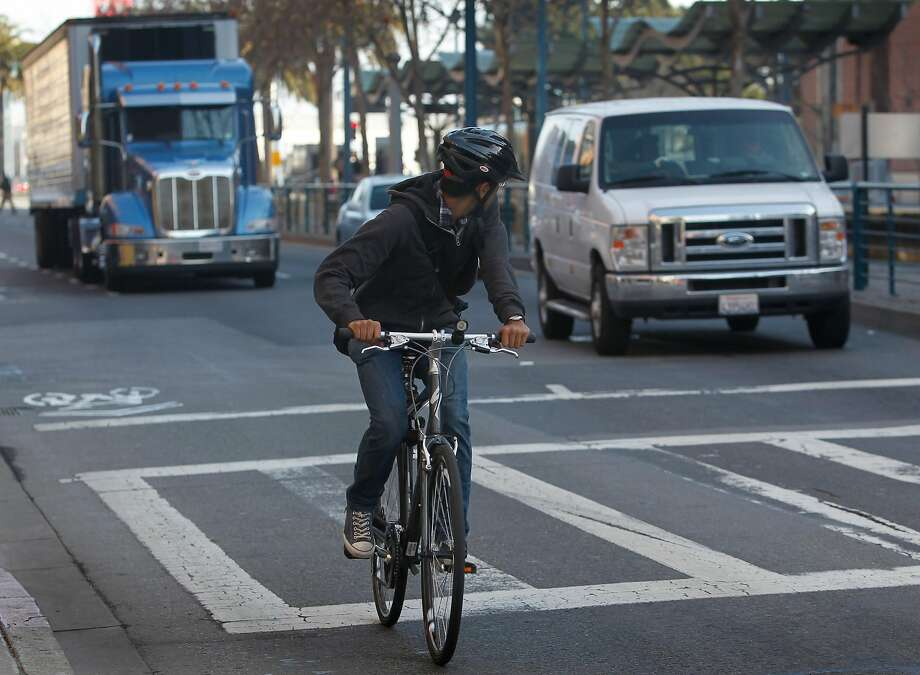 A bicyclist keeps an eye on traffic as he merges with vehicles at the end of a bike lane on King Street between 2nd and 3rd streets in San Francisco, Calif. on Tuesday, Feb. 12, 2013. A woman riding her bicycle was struck and killed after she collided with a cement truck last weekend. Photo: Paul Chinn / The Chronicle
