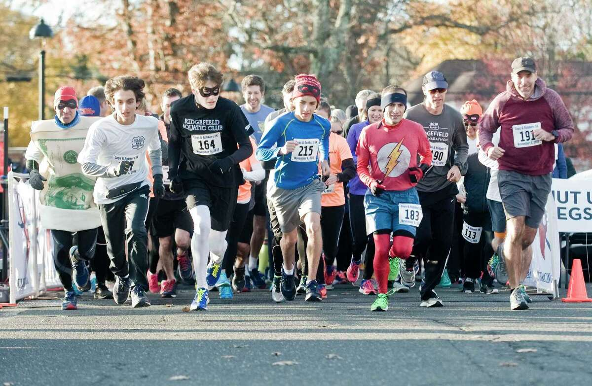 Runners take off from the starting line of the annual Cops and Robbers 5K at The Ridgefield Playhouse in November 2018.