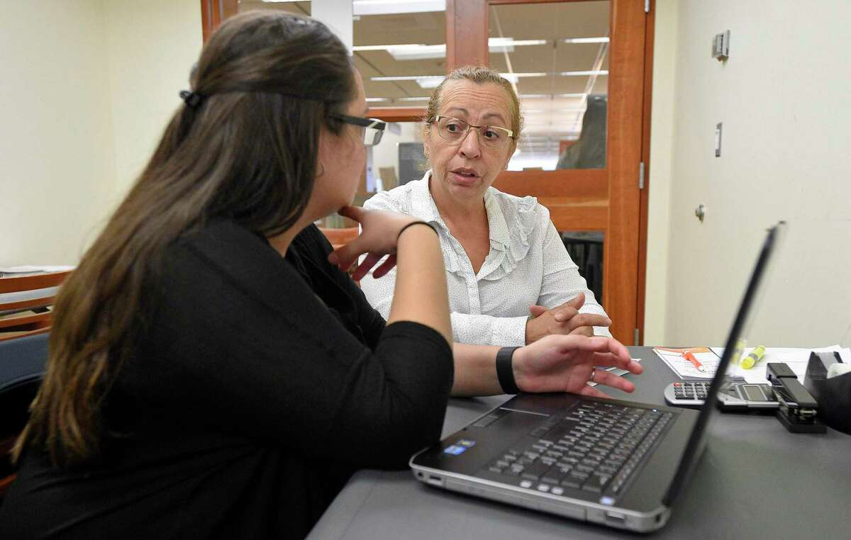 An Access Health CT enrollment specialist assists a Stamford, Conn. resident enroll for health insurance coverage, in November 2017. The 2019 open enrollment season begins Nov. 1.
