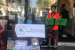 """Tyler Hilford and Aakarsh Patel, left to right, perform as the """"Musical Rescuers"""" in front of Kafo on Main Street."""