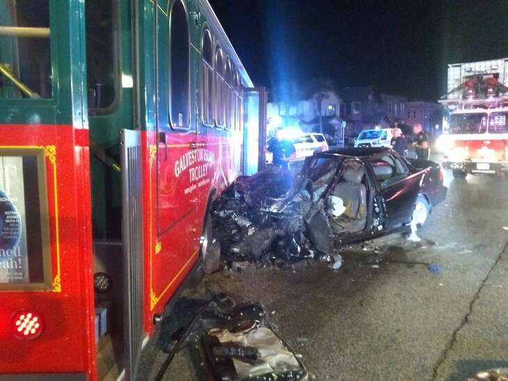 A 30-year-old man and his dog died after the car he was driving became pinned underneath a Galveston trolley bus when he struck it, Galveston city officials said.