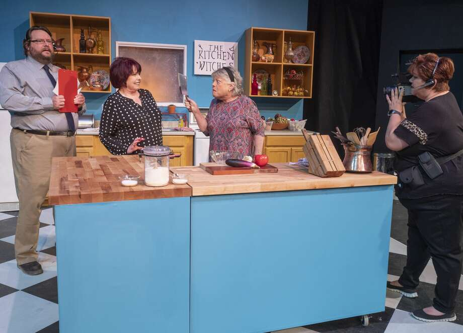 Gail Theobald as Isobel Lomax and Trudie Thomason as Dolly Biddle argue in the kitchen as Nicholas McRae as Stephen Bidddle and Laura Abbott as Robin films the encounter 10/22/19 in a scene from MCT's production of Kitchen Witches. Tim Fischer/Reporter-Telegram Photo: Tim Fischer/Midland Reporter-Telegram