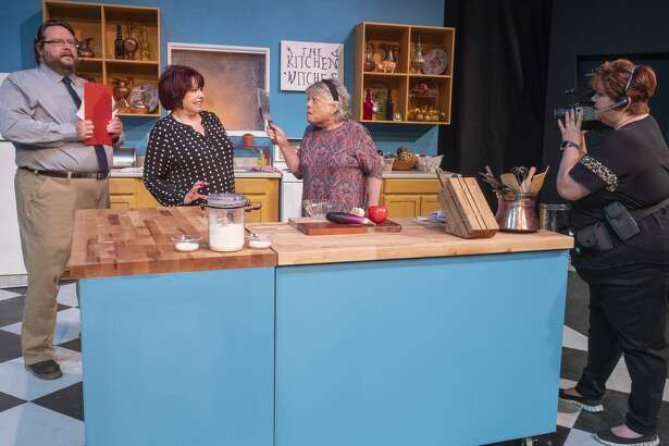 Gail Theobald as Isobel Lomax and Trudie Thomason as Dolly Biddle argue in the kitchen as Nicholas McRae as Stephen Bidddle and Laura Abbott as Robin films the encounter 10/22/19 in a scene from MCT's production of Kitchen Witches. Tim Fischer/Reporter-Telegram