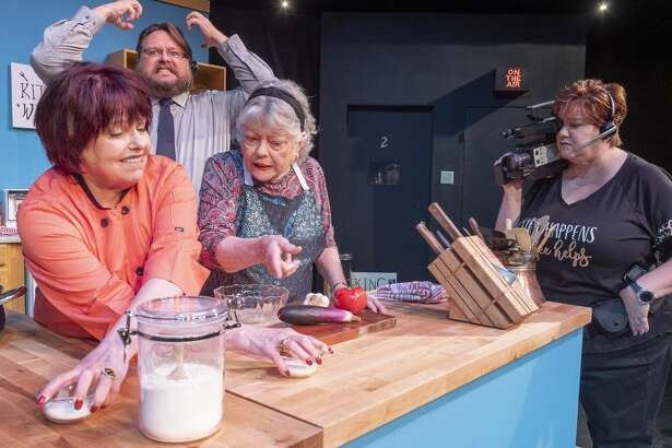 Gail Theobald as Isobel Lomax and Trudie Thomason as Dolly Biddle argue in the kitchen as Nicholas McRae as Stephen Bidddle throws a fit and Laura Abbott as Robin films the encounter 10/22/19 in a scene from MCT's production of Kitchen Witches. Tim Fischer/Reporter-Telegram