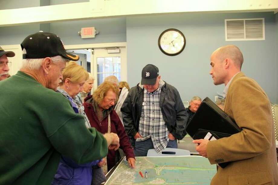 Scot Lautzenheiser, right, an architect with Wade Trim, hears comments from locals about the Grindstone Marina. Wade Trim drew up site plans for a renovation to the harbor. (Robert Creenan/Huron Daily Tribune)
