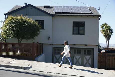 Dorothy Krause walks past her home with solar panels installed on the roof in Oakland, Calif. on Tuesday, Oct. 22, 2019.