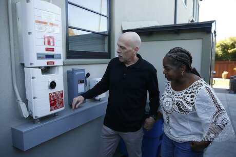 Derek and Dorothy Krause check the utility panel for the solar energy and backup system installed at their home in Oakland, Calif. on Tuesday, Oct. 22, 2019.
