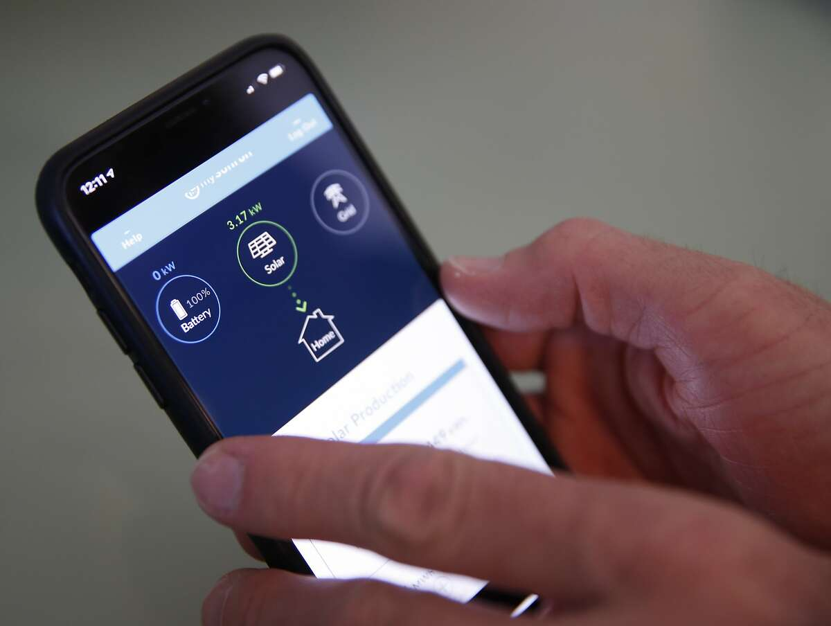 Derek Krause uses an app to monitor the solar energy and backup battery system installed at his home in Oakland, Calif. on Tuesday, Oct. 22, 2019.