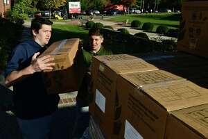 Hundreds of volunteers including Patrick Cummins and Anthony Gili help package meals for Wilton's Wi-ACT Interfaith Committee the 6th annual Rise Against Hunger meal packaging event Saturday, October 19, 2019, at Wilton Presbyterian Church in Wilton, Conn. Four shifts of nearly 750 volunteers will load a shipping container destined for Somalia with the completed meals.