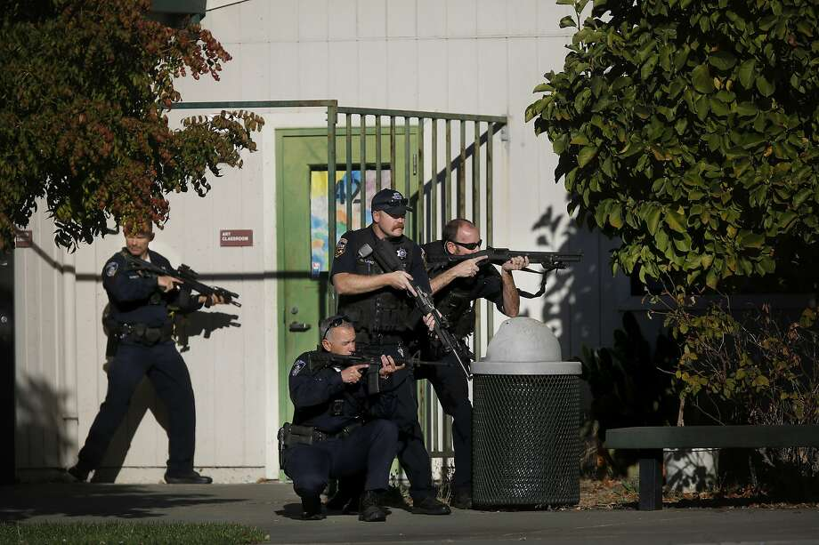 Santa Rosa police officers hold guns as they search the campus of Ridgway High School for suspects after a shooting at the school in Santa Rosa, Calif., Tuesday, Oct. 22, 2019. (Beth Schlanker/The Press Democrat via AP) Photo: Beth Schlanker, Associated Press