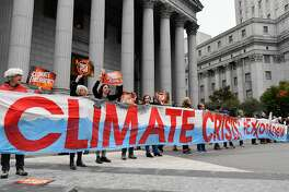 Climate activists protest on the first day of the ExxonMobil trial outside the New York State Supreme Court building on October 22, 2019 in New York City. - Charges that Exxon Mobil misled investors on the financial risks of climate change will be heard in court after a New York judge gave the green light for a trial. (Photo by Angela Weiss / AFP) (Photo by ANGELA WEISS/AFP via Getty Images)