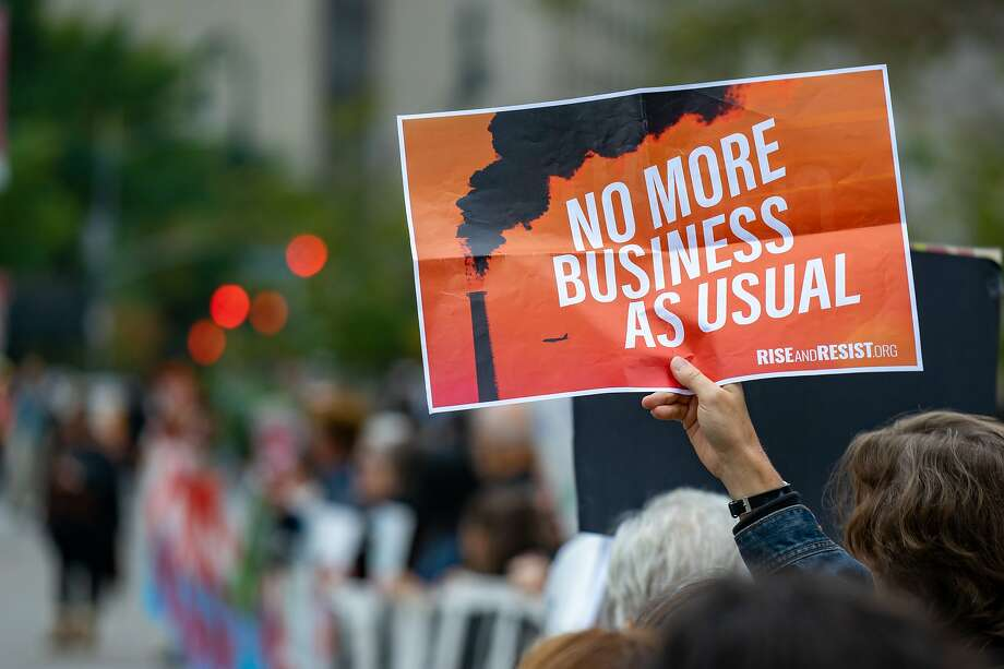 """A demonstrator holds a sign that reads """"No More Business As Usual"""" during a protest on the first day of the ExxonMobil Corp. trial outside the New York State Supreme Court building in New York, U.S., on Tuesday, Oct. 22, 2019. On Tuesday, New York's attorney general squares off againstExxon Mobil Corp.in a three-week trial that will focus on whether Exxon cooked its books when it came to internal financial projections that incorporate the cost of global warming. Photographer: David 'Dee' Delgado/Bloomberg Photo: David 'Dee' Delgado, Bloomberg"""