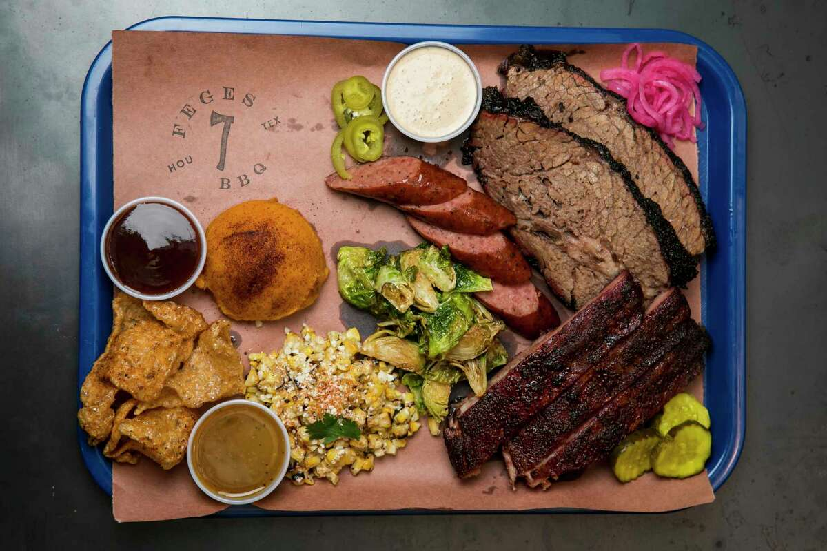 A barbecue platter featuring the Texas Trinity - brisket, pork ribs and sausage - with sides at Feges BBQ