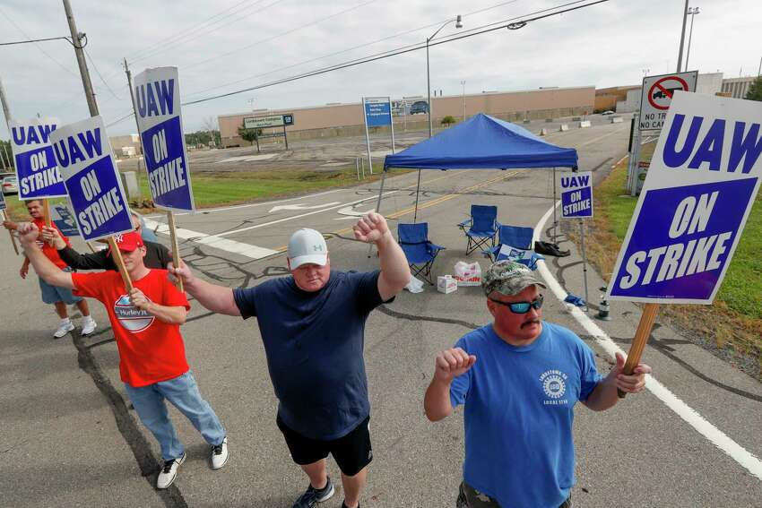 FILE - In this Sept. 16, 2019, file photo picketers carry signs at one of the gates outside the closed General Motors automobile assembly plant in Lordstown, Ohio. Many from Lordstown, Ohio, and near Baltimore and Detroit are opposing a deal that could end a 37-day strike that crippled GMa€™s U.S. production and cost the company an estimated $2 billion. (AP Photo/Keith Srakocic, File)