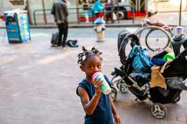 Homeless child Leaa Pree, 3 stands on Market Street drinking a bottle as her mother (not pictured) waits nearby in San Francisco, California, on Monday, Oct. 7, 2019. Leaa and her family have just received permanent housing.