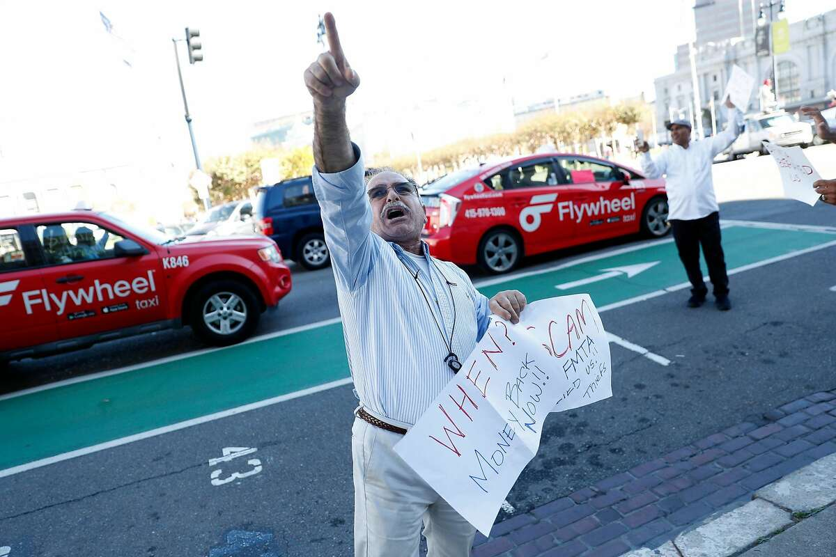 Taxi driver Alan Khani points towards City Hall as he joins protest in San Francisco, Calif., on Tuesday, October 22, 2019.