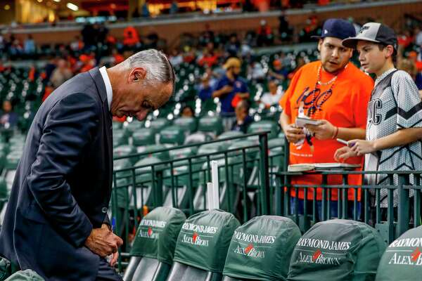 MLB commissioner Rob Manfred signs a baseball before Game 1 of the World Series at Minute Maid Park in Houston on Tuesday, Oct. 22, 2019.