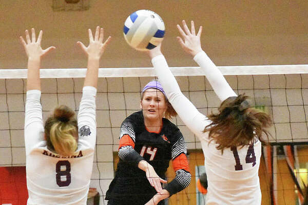 Edwardsville senior Maddie Isringhausen slams one of her six kills through the Belleville West block during the first game Tuesday inside Lucco-Jackson Gymnasium.