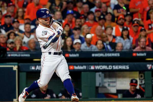 Houston Astros second baseman Jose Altuve (27) hits a single to left field during the first inning of Game 1 of the World Series at Minute Maid Park in Houston on Tuesday, Oct. 22, 2019.