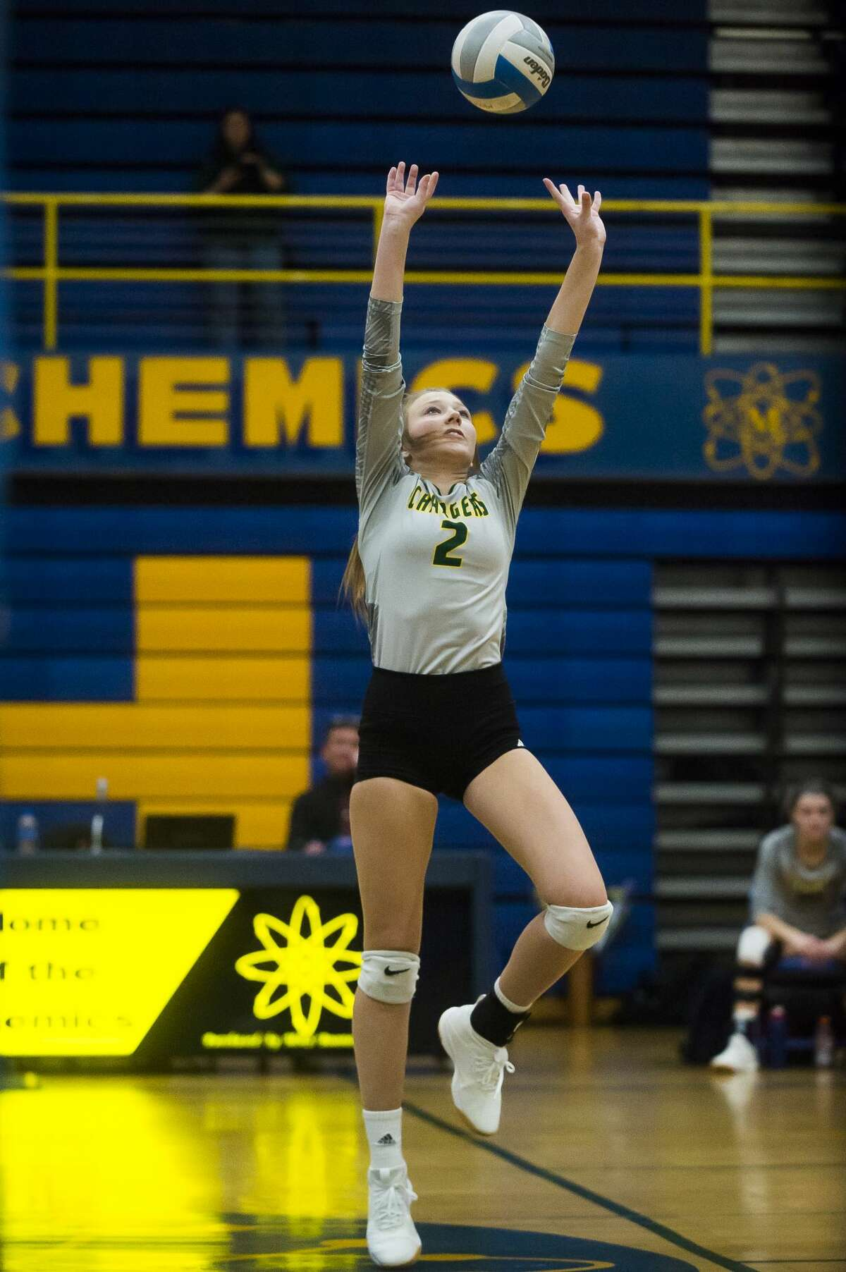Dow's Laura Hershauer sets the ball during a match against Midland Tuesday, Oct. 22, 2019 at Midland High School. (Katy Kildee/kkildee@mdn.net)