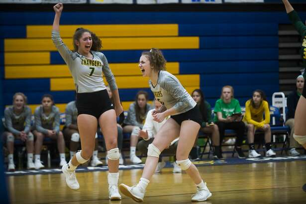 Dow's Hailey Tanis, left, and Francesca Queary, right, celebrate a point during a match against Midland Tuesday, Oct. 22, 2019 at Midland High School. (Katy Kildee/kkildee@mdn.net)