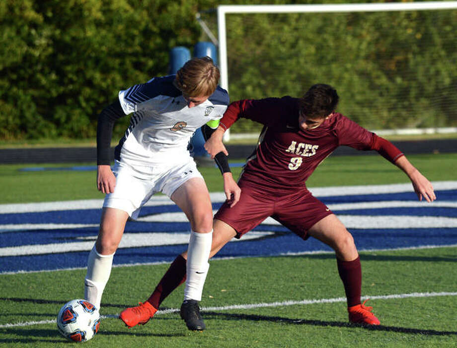Father McGivney's Jonah Mitan, left, battles a Mount Carmel player for the ball during the first half of Tuesday's game against Mount Carmel in the semifinals of the Class 1A Columbia Sectional.